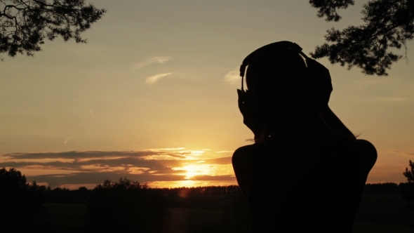 VideoHive Woman Putting on the Headphones Listening To Music and Dancing in the Forest 18950117