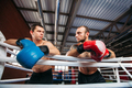 Two boxers look at each other after training.