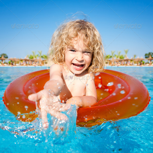 Happy child playing in blue water - Stock Photo - Images
