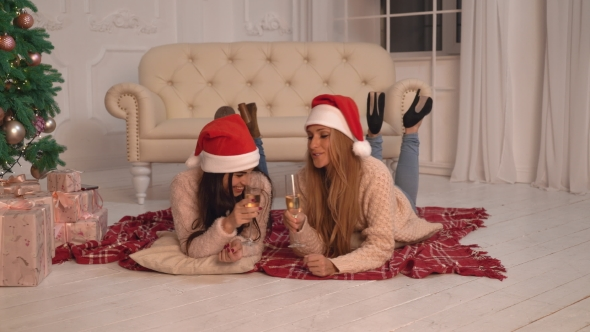 VideoHive Women Drinking Champagne Near Christmas Tree at Home 18959896