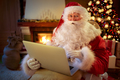 Santa Claus sitting by the fireplace with laptop