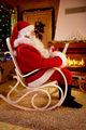 Santa Claus relaxing at home sitting in rocking chair