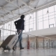 Unrecognizable Man with Suitcase Hurrying. Businessman Runing with Laggage in Airport Terminal or