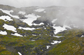 Norwegian rocky mountain landscape with snow and fog. Norway trekking. Horizontal