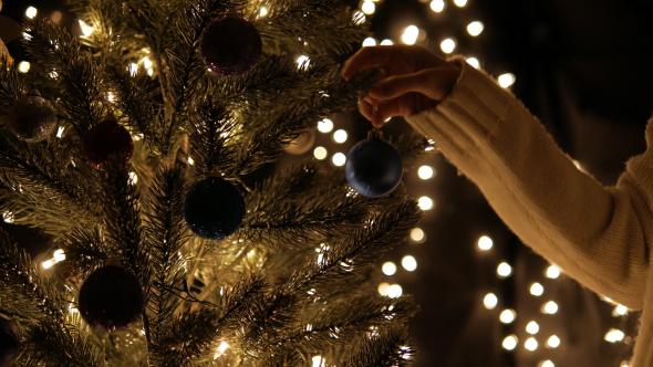 Hangs Christmas Ball On Tree