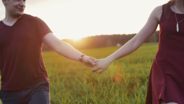 VideoHive Couple Walk in Beautiful Place at Sunset Hold Hands Lovers Hug Tenderly Woman Wears Glasses 18977365