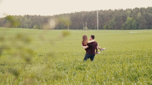 VideoHive Loving Couple Swirl Around in a Field Happy Man and Woman Look at Each Other Womans Hair Sway in 18978973