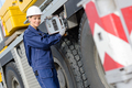 Woman operating controls on side of heavy goods vehicle