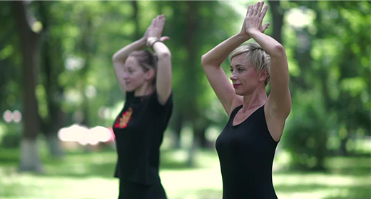 Two women doing exercises outdoors