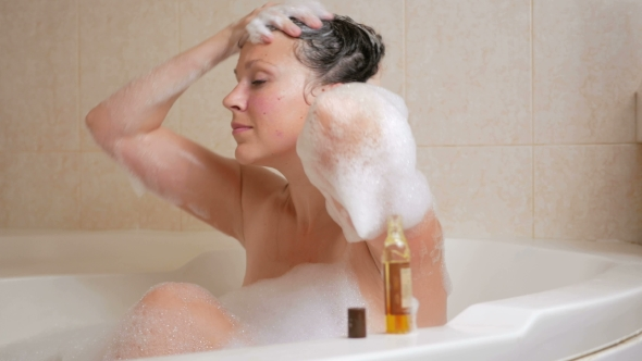 VideoHive Young Girl Takes a Bath with Foam and Washing Hair with Shampoo 19012101