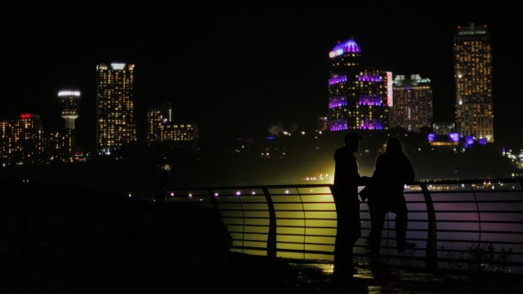VideoHive Silhouettes of Men and Women Against the Background of Skyscrapers in a Night City Communicate 19012529