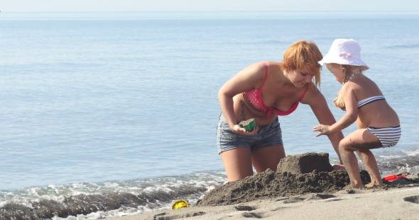 VideoHive Mom and Daughter Are Building a Sand Castle 19016693