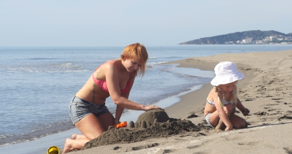 VideoHive Mom and Daughter Are Building a Sand Castle 19016762