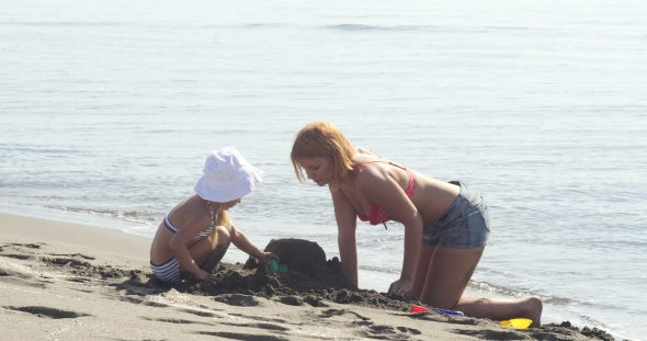 VideoHive Mom and Daughter Are Building a Sand Castle 19016796