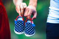 wife and husband holding baby shoes