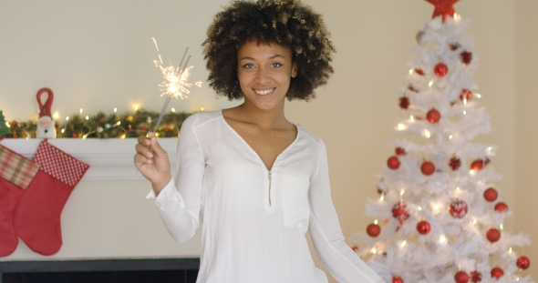 Download Pretty Young Woman Burning a Christmas Sparkler nulled download