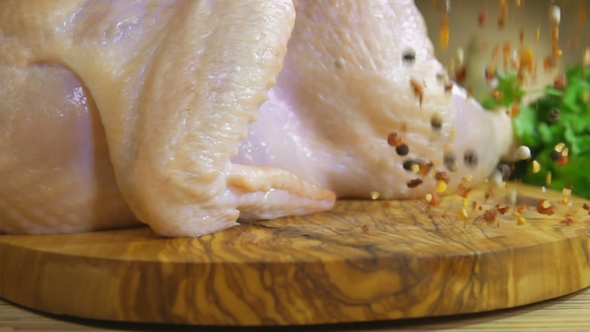 Download Spices Are Falling on a Wooden Board with Raw Chicken nulled download