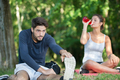 couple stretching outdoors while drinking water