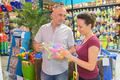 young parents buying baby toy