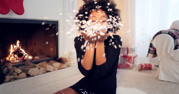 Young Woman Blowing Christmas Confetti