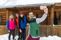 People Group Taking Selfie Photo On Smart Phone Near Wooden Country House Winter Snow Resort Cottage