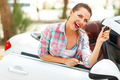 Woman standing near convertible with keys in hand - concept of b