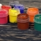 A Lot of Varicolored Paint Gouache Jars with Brushes on Wooden Background