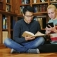 Friends Sitting on the Floor in the Library. A Man Holding an Open Book, a Woman Used a Tablet