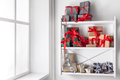 Christmas gift boxes on white shelves at wall background
