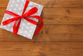 Present in gift box on wood background with copy space
