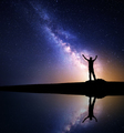 Milky Way and silhouette of a standing happy man