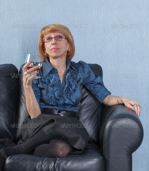 woman with a glass brandy on couch - Stock Photo - Images