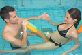 husband and pregnant wife training at swimming pool
