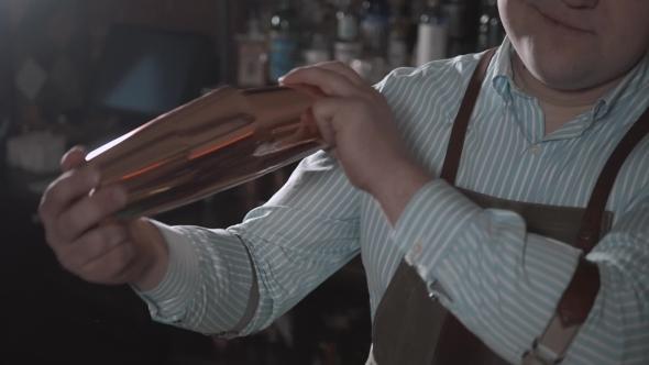 VideoHive Handsome Barman Smiling at Camera Making a Cocktail at the Bar and Shake 19122451