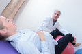 old male doctor with pregnant woman sitting on fitness ball