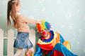 Little girl pulls clown hair.