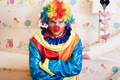 Angry clown with rainbow colored hairstyle.