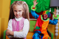 Upset little girl standing in the playroom.