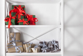 Holiday presents, gift boxes on white shelves at wall background