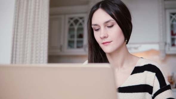 VideoHive Portrait of a Beautiful Young Brunette Woman Uses Laptop in a Bright Dining 19147466