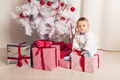 Cheerful little baby boy playing near the Christmas tree