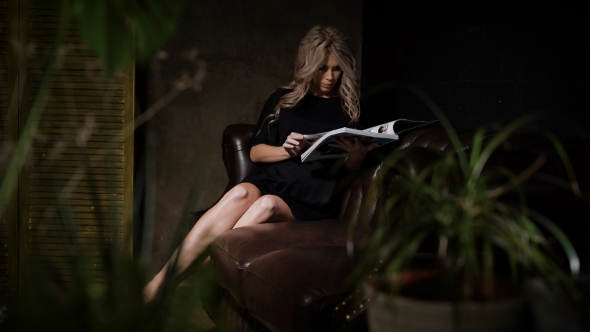 VideoHive Beautiful Pregnant Blonde in Black Dress Sitting in the Dark Room on the Big Brown Leather Sofa with 19155071