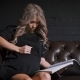 Young Pregnant Woman in Black Dress Sitting on the Big Brown Couch Touching Her Belly Lovingly