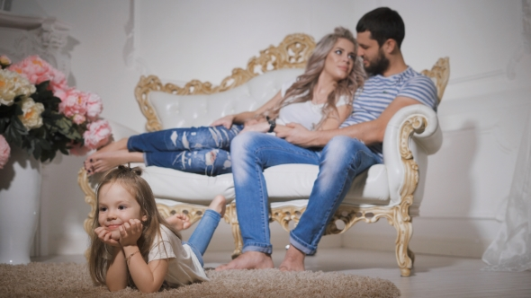 VideoHive of Happy Family Expecting New Baby with Little Smiling Girl in the Foreground Lying on the 19155349