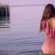 Lonely Woman in a Pink Dress Sitting on the Bank of the Pond.