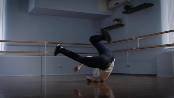 VideoHive Professional Breakdancer Performs Complex Dance Exercise on the Floor of the Dance Studio Young Boy 19158526