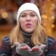 Happy Carefree Woman With Blonde Hair Sends An Air Kiss Over Christmas Lights Background