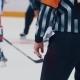 Hockey Referee Looks on Players