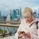 A Young Woman Uses a Smartphone. Brooklyn Bridge in New York, Urban Background