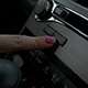 Female Hand Typing Media Button in Car